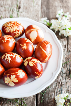 Easter Eggs in white Plate on Wooden Table, Decorated with Natural Fresh Leaves and Boiled in Onions Peels Standard-Bild