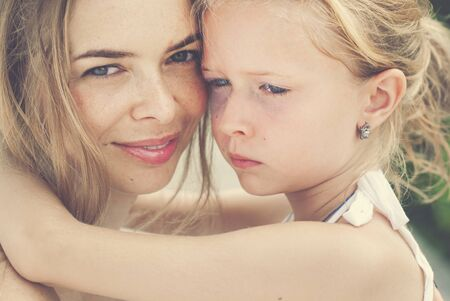 pre adult: Hugging smiling mother and daughter. Family, child and happiness concept. Toned image Stock Photo