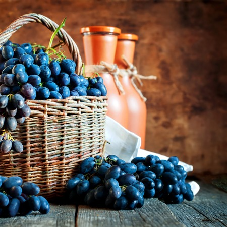 wine country: Blue Grapes in Rural Basket on Wooden Background and Terracotta Bottles of Wine. Country style Stock Photo