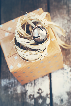 cristmas card: Christmas Gift with Jingle Hand Bell and Natural Twine on Wooden Background. Toned image