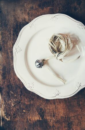 hand bell: Christmas Hand bell on Vintage Plate on Wooden Table. Warm Toned effect Stock Photo