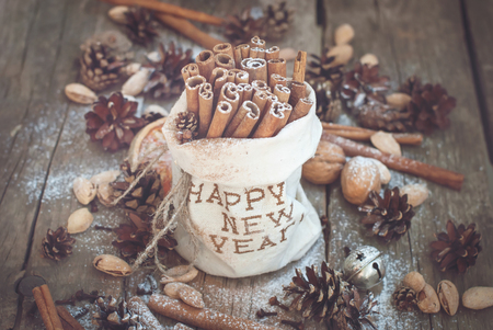 linen bag: Christmas Ingredients on Wooden Background. Sticks of Cinnamon in Linen Bag Embroidered with Happy New Year, Pine cones, Walnuts. Toned