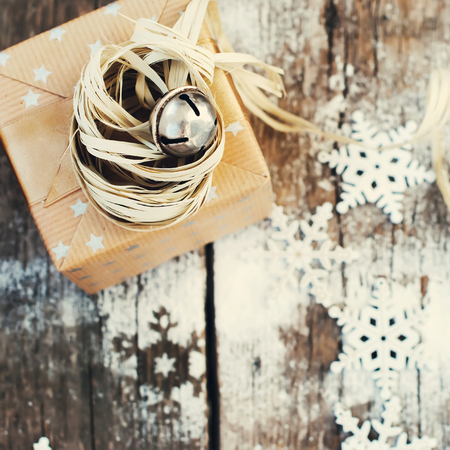hand bell: Holiday Gift with Jingle Hand Bell and Natural Twine on Wooden Snow Background. Toned image Stock Photo