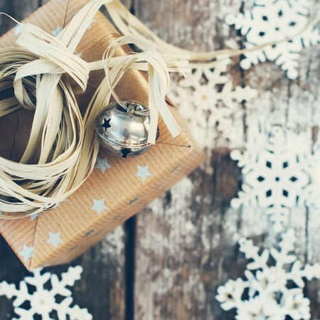 cristmas card: Christmas Card with Holiday Box, Jingle Bell and Natural Twine on Wooden Snow Background. Toned image Stock Photo
