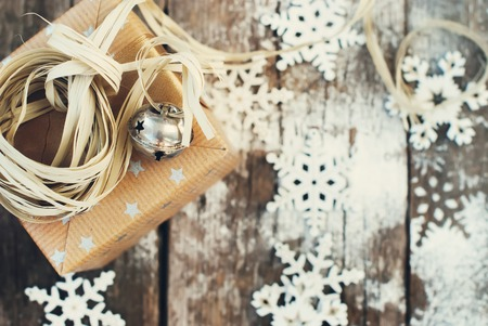 Jingle Hand Bell and Natural Twine as Decor on Christmas Box. Wooden Background with Snowflakes. Toned image