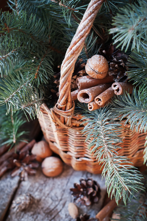 Natural Christmas Decor in a Basket. Nuts, Fir Tree, Cinnamon, Pine cones on Wooden Background. Rustic style