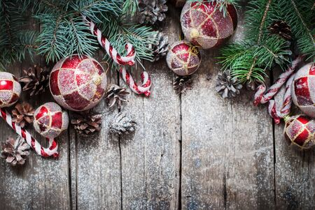a cane: Christmas Vintage Fir Tree Toys, Red Balls, Coniferous, Candy Cane, Pine Cones as Decor on Wooden Planks