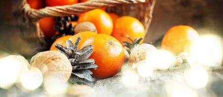 festive food: Christmas Light with Basket of Festive Food, Fruits and Nuts. Tangerines, Pine cones, Walnuts, Almonds are scattered on wooden background