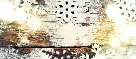 new idea: Bright Light with White Wooden Decorative Snowflakes on Old Vintage Background, as the Christmas Decor. Tinted photo