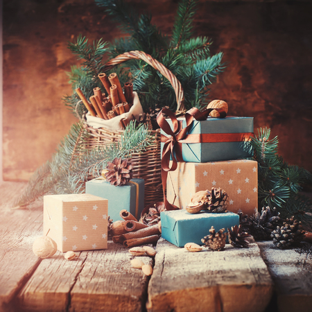 festive pine cones: Festive Gifts with Boxes, Coniferous, Basket, Cinnamon, Pine Cones, Wallnuts on Wooden Background. Christmas Presents Toned in Vintage Style Stock Photo