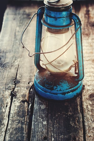 memoirs: Vintage Dirty Blue Oil lantern on Wooden Background. Toned. selective focus