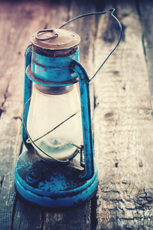 chronicle: Vintage Dirty Blue Oil Lamp on Wooden Background. Toned. selective focus