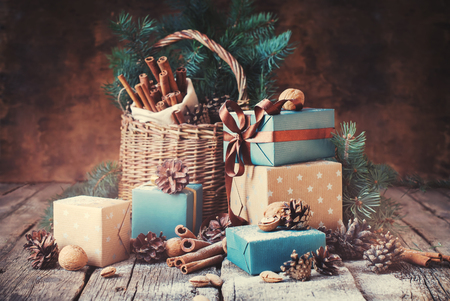 Festive Gifts with Boxes, Coniferous, Basket, Cinnamon, Pine Cones, Wallnuts on Wooden Background. Christmas Presents Toned in Vintage Style Archivio Fotografico