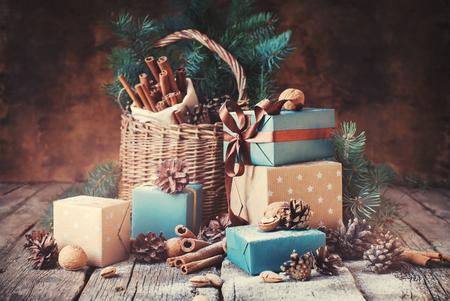 adviento: Regalos festivos con Cajas, coníferas, cesta, canela, conos del pino, wallnuts sobre fondo de madera. Regalos de Navidad virada en estilo vintage