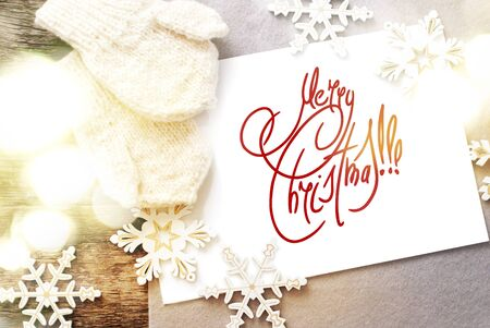 Festive Light on Card with Message Merry Christmas on the letter isolated on white, decorated snowflakes and mittens