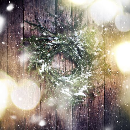 vintage door: Green Natural Wreath on Wooden Background with drawing Falling Snow. Toned image with Light Boke