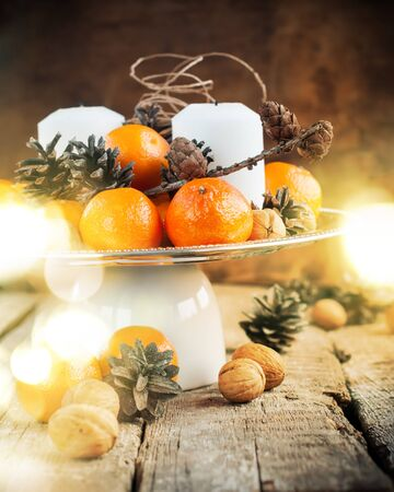 cristmas card: Festive Table with Tangerines, Pine cones, Walnuts, Candles on the Tray on Wooden Background, holiday decoration with Christmas Light Stock Photo
