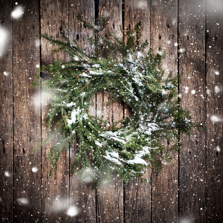 country christmas: Green Natural Wreath on Wooden Background with drawing Falling Snow. Vintage Style