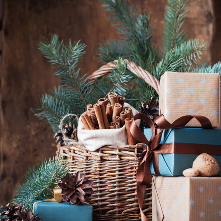 festive pine cones: Christmas Card. Festive Gifts with Boxes, Coniferous, Basket, Cinnamon, Pine Cones, Wallnuts on Wooden Background Stock Photo
