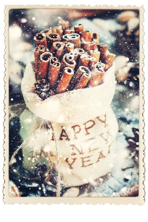 linen bag: Retro Card with Sticks of Cinnamon in a Linen Bag with Embroidered Happy New Year on Christmas Table, other christmas ingredients, Pine cones, Walnuts. Toned, Drawn snow