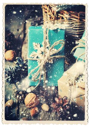 festive pine cones: Retro Card with Festive Boxes with Cozy Country Decor, Blue Paper, Snowflakes, Pine Cones, Walnuts, Almond, Linen Cord on Wooden Table. Toned. Drawn Snow