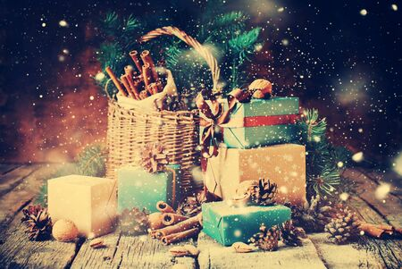 basket: Festive Gifts with Boxes, Coniferous, Basket, Cinnamon, Pine Cones, Walnuts on Wooden Background. Vintage Style with Drawn Snowfall