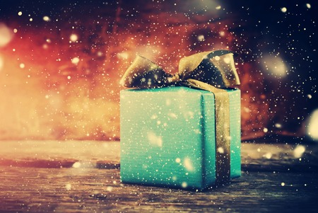 christmas bow: Christmas Gift. Festive Box on Wooden Background with Drawn Snow. Toned