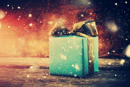 Weihnachtsgeschenk. Festliche Box auf Holzuntergrund mit Gezeichnet Schnee. tonte Standard-Bild - 46933422