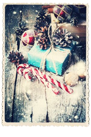 festive pine cones: Retro Card with Festive Box, Gifts, Natural Twine, Balls, Pine Cones, Walnuts, Fir Tree Toys on Wooden Background. Toned. Vintage Style with Drawn Snowfall Stock Photo