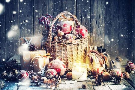 country christmas: Christmas Gifts. Basket, Burning Candle, red balls, pine cones, snowflakes on Wooden Background. Vintage style with Drawn Snowfall