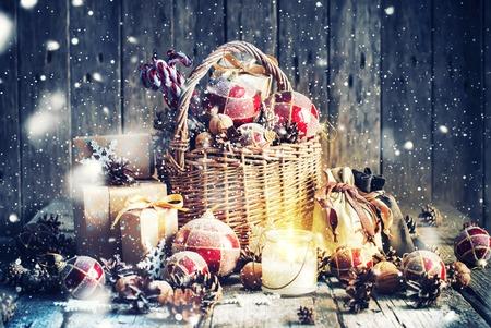 cajas navide�as: Regalos de Navidad. Cesta, vela ardiente, bolas rojas, pi�as, los copos de nieve en el fondo de madera. estilo de la vendimia con las nevadas Drawn Foto de archivo