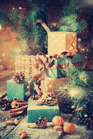 in the basket: Christmas Gifts with Boxes, Coniferous, Basket, Cinnamon, Pine Cones, Walnuts on Wooden Background. Vintage Style with Drawn Snowfall
