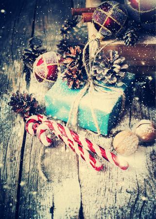 cajas navide�as: Azul de vacaciones con caja de regalo y cordeles natural, Balones, conos de pino, nueces, abeto Juguetes del �rbol en el fondo de madera. Virada. Estilo de la vendimia con las nevadas Drawn