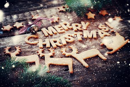 Karte mit Gingerbread Cookies. Baked Letters Frohe Weihnachten, Glocke, Tanne, Figuren der Deers, Schlitten, Sterne. Getönten Standard-Bild