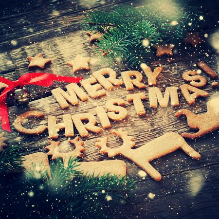 Karte mit Frohe Weihnachten von Lebkuchen auf Holztisch. Glocke, Tanne, Buchstaben und Zahlen Deers, Schlitten, Sterne. tonte Standard-Bild - 46933536