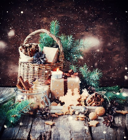festive pine cones: Festive Gifts with Boxes, Coniferous, Basket, Cinnamon, Pine Cones, Walnuts on Wooden Background. Vintage Style with Drawn Snow