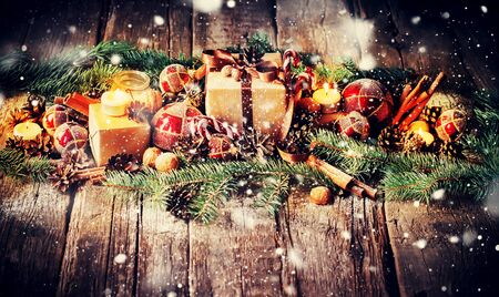 Festive Christmas Composition with Gifts, Boxes, Balls, Pine Cones, Wallnuts, Fir Tree Toys and Burning Candles on Wooden Background.  Drawn Snow