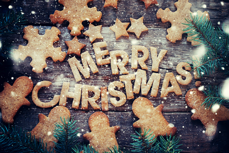 galletas: Al horno Cartas Feliz Navidad, Campana, Abeto, figuras de ciervos, trineo, estrellas. Tarjeta con las galletas del pan. Entonado Foto de archivo