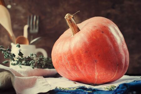 larder: Fresh Pumpkin on a Napkin on Wooden Table with Vintage Crockery. Toned image