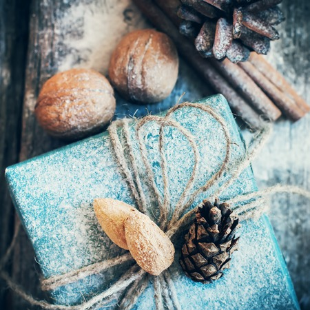 holiday home: Christmas Holiday Box with Linen Cord, Decorative Snow, Almond, Natural Gifts on Wooden Background. Toned image. Vintage style