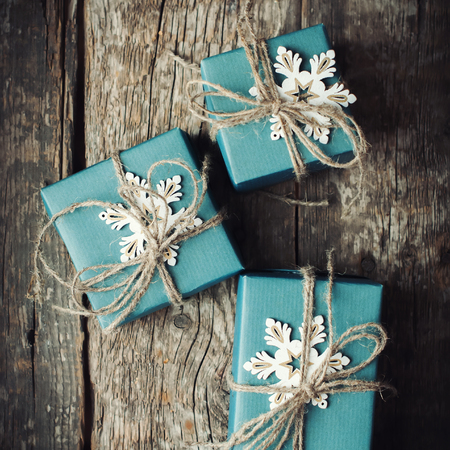 Three Festive Boxes in Blue Paper Decorated with Snowflakes and Linen Cord on Wooden Table. Top View