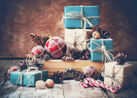 Holiday Christmas Gifts with Boxes and Natural Twine, Balls, Pine Cones, Wallnuts, Fir Tree Toys on Wooden Background. Toned image