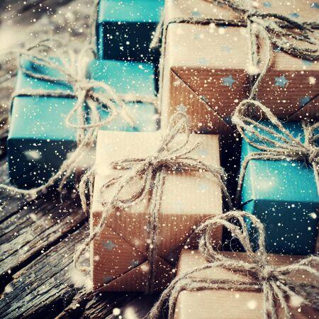 cajas navide�as: Cajas festivas con el cordel de lino. Regalos naturales en el fondo de madera. Las nevadas dibujado. tonificado