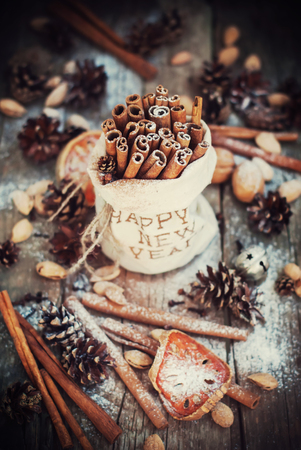 linen bag: Sticks of Cinnamon and other Christmas Ingredients, Pine cones, Walnuts in Linen Bag with Embroidery Happy New Year on Wooden Background. Vintage Christmas Composition Stock Photo