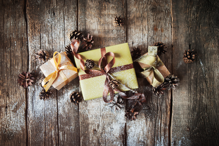 festive pine cones: Festive Boxes are Packed into a Green Paper with Brown Ribbon on Wooden Table. Decorated with Pine Cones