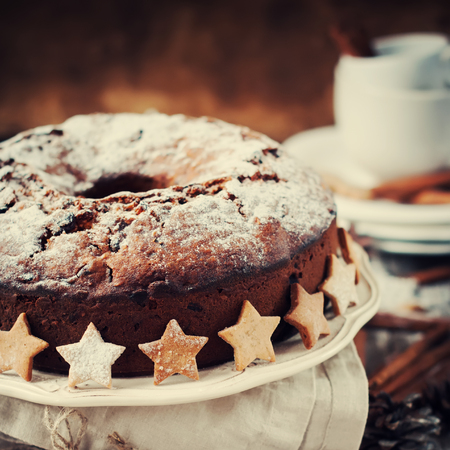 cioccolato natale: Christmas Cake with Powered Sugar on Vintage Plate with Festive Decoration Star on Wooden Table