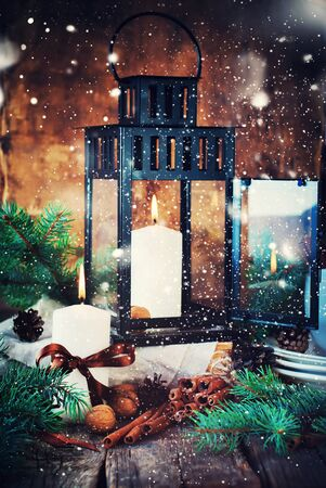 cristmas card: Christmas Card with Lantern. Festive Dishware, Candles, Cinnamons, Pine cones, WalnutsFir Tree on the Wooden Table in Festive Composition. Effect Drawn Snow Stock Photo