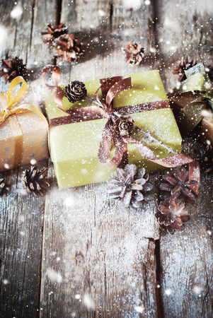 Christmas Boxes Decorated with Brown Ribbon, Pine cones on Wooden Background. Covered with artificial snow