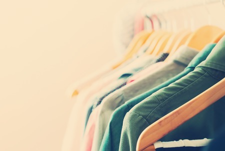 casual clothing: Pastel Color Clothes. Female Dresses on Open Clothes Rail. Toned image