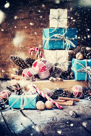 Holiday Christmas Gifts with Boxes, Twine, Balls, Pine Cones, Walnuts, Fir Tree Toys on Wooden Background. Drawn Snow